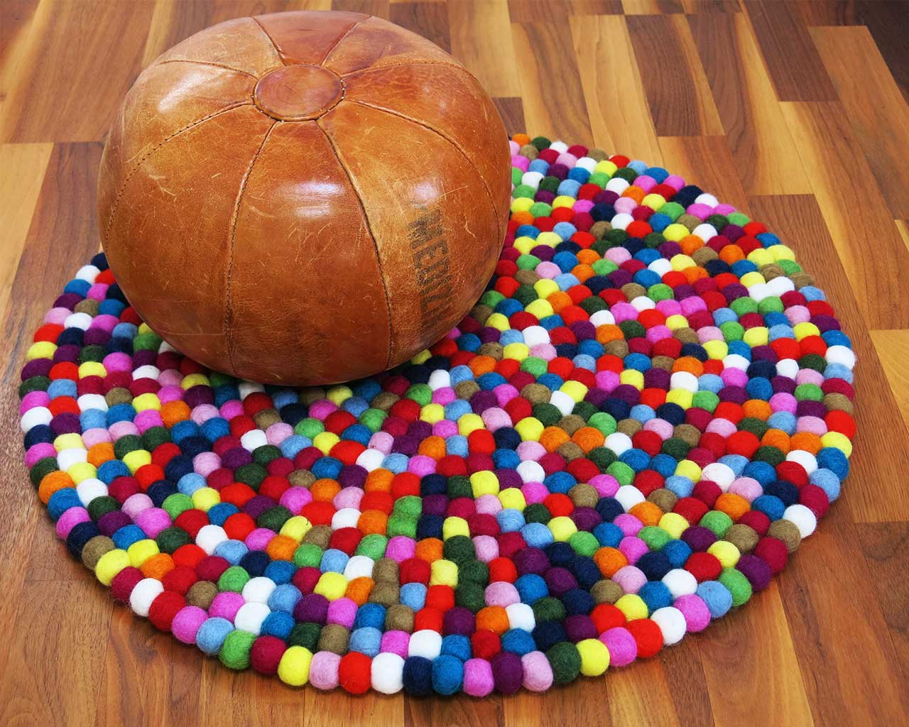 brown pouf with felt ball rug